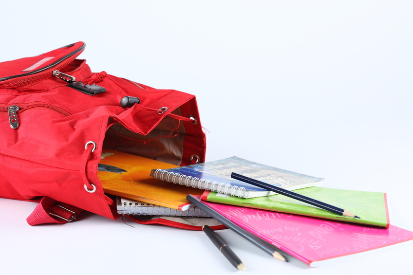 Open backpack school supplies spilling out